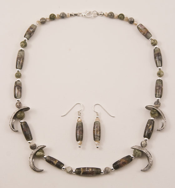 Necklace with grey and earthtone lampworked beads and foldformed silver ornaments