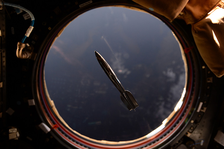 The Mini Hugo Rocket floats in the International Space Station in front of a window overlooking the Earth.