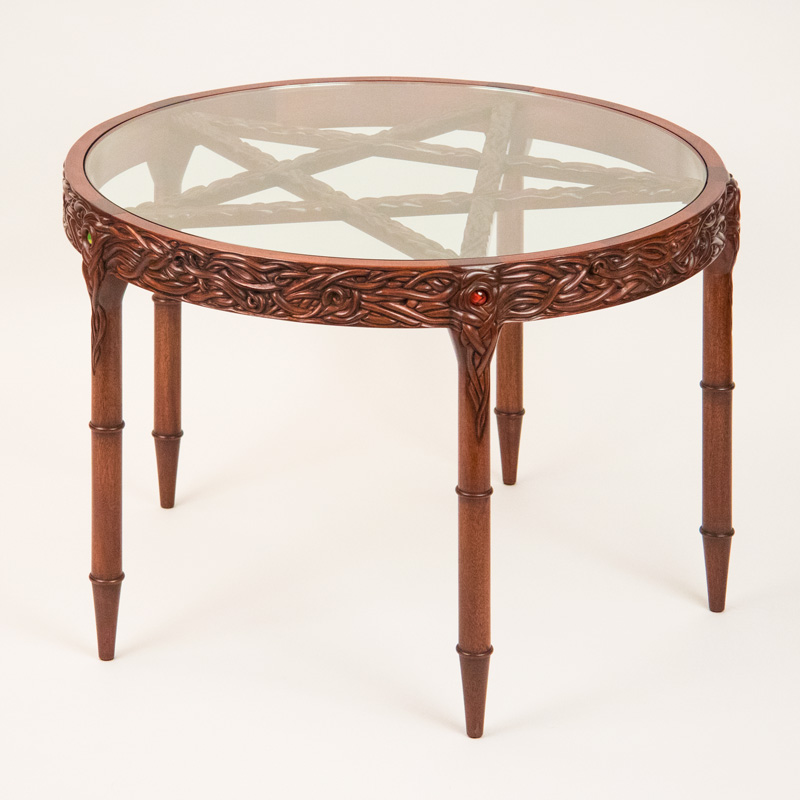 Pentacle Table - Round with glass top, tendril carved rim, turned and carved legs, and carved pentagram under the glass. One inch glass marbles are embedded in the top of each leg.