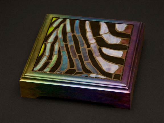 Stained glass mosaic trivet shading in greens, blues and purples, with painted frame.